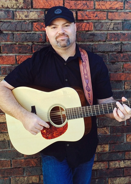 sponsored artist Adam Chowning with his Thompson guitar