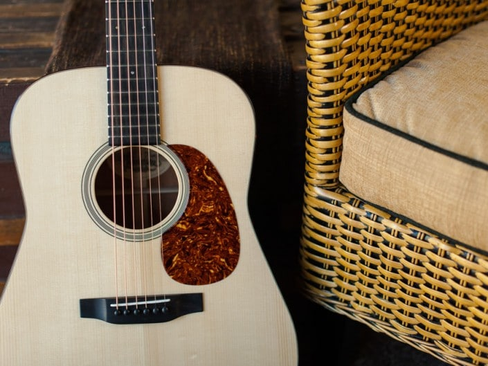 Acoustic dreadnought guitar handcrafted of mahogany back and sides with an adirondack top. closeup