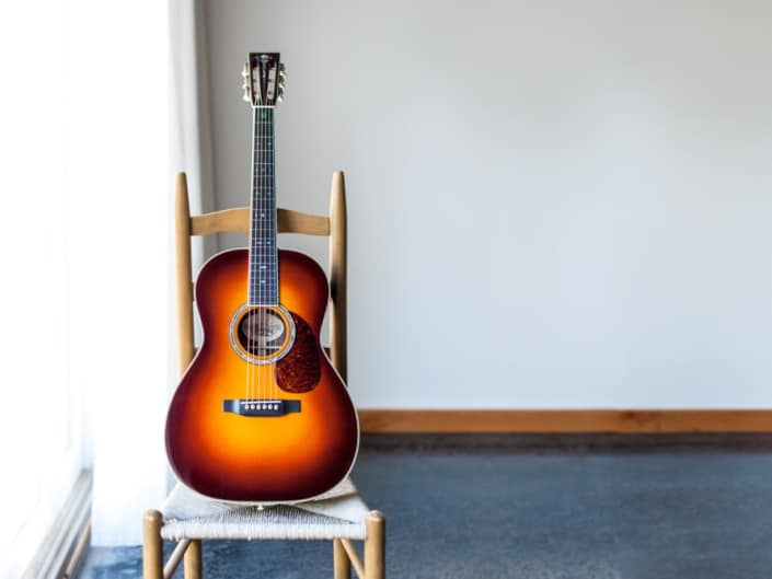12 Fret 000 acoustic guitar handcrafted from Adirondack Spruce and Brazilian Rosewood. On a chair
